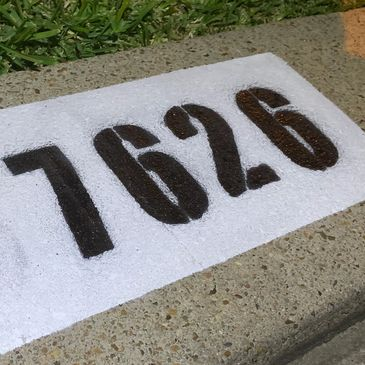 Curb Painting with large black numbers and a marine design.