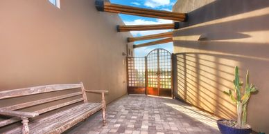Enter through this charming courtyard with a custom handcrafted iron gate, Metal bands and latilla b