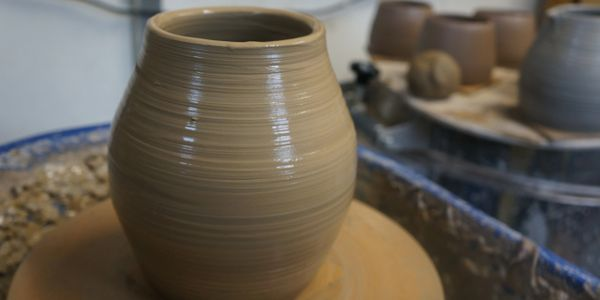 a freshly thrown curvy pot sitting glistening on the wheel, with more thrown pots in background
