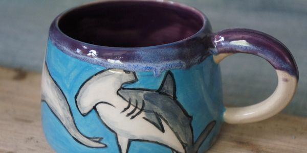 A hand painted hammerhead shark mug with blue background and purple rim