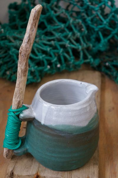 a curvy green jug with white rim , driftwood handle held on with green ghost rope