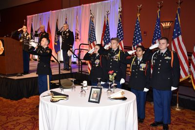 Photo of Guthrie High School JROTC cadets with POWMIA table and all saluting.
