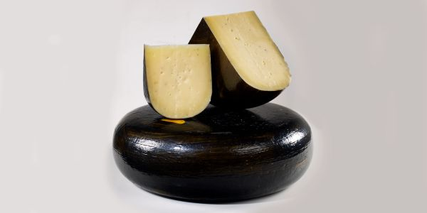 A wheel, a quarter and a wedge of Mountainoak Truffle  cheese.