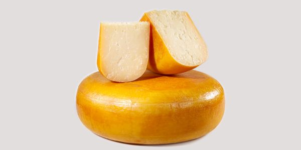 A wheel, a quarter and a wedge of Farmstead GOLD Gouda cheese.