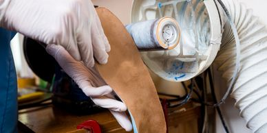 Dr. Sables builds and finishes a pair of custom foot orthotics.  Your orthotics are built in-house.