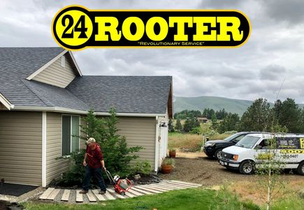 24 rooter of yakima plumbing company. plumber carrying a drain cleaning machine at residential home