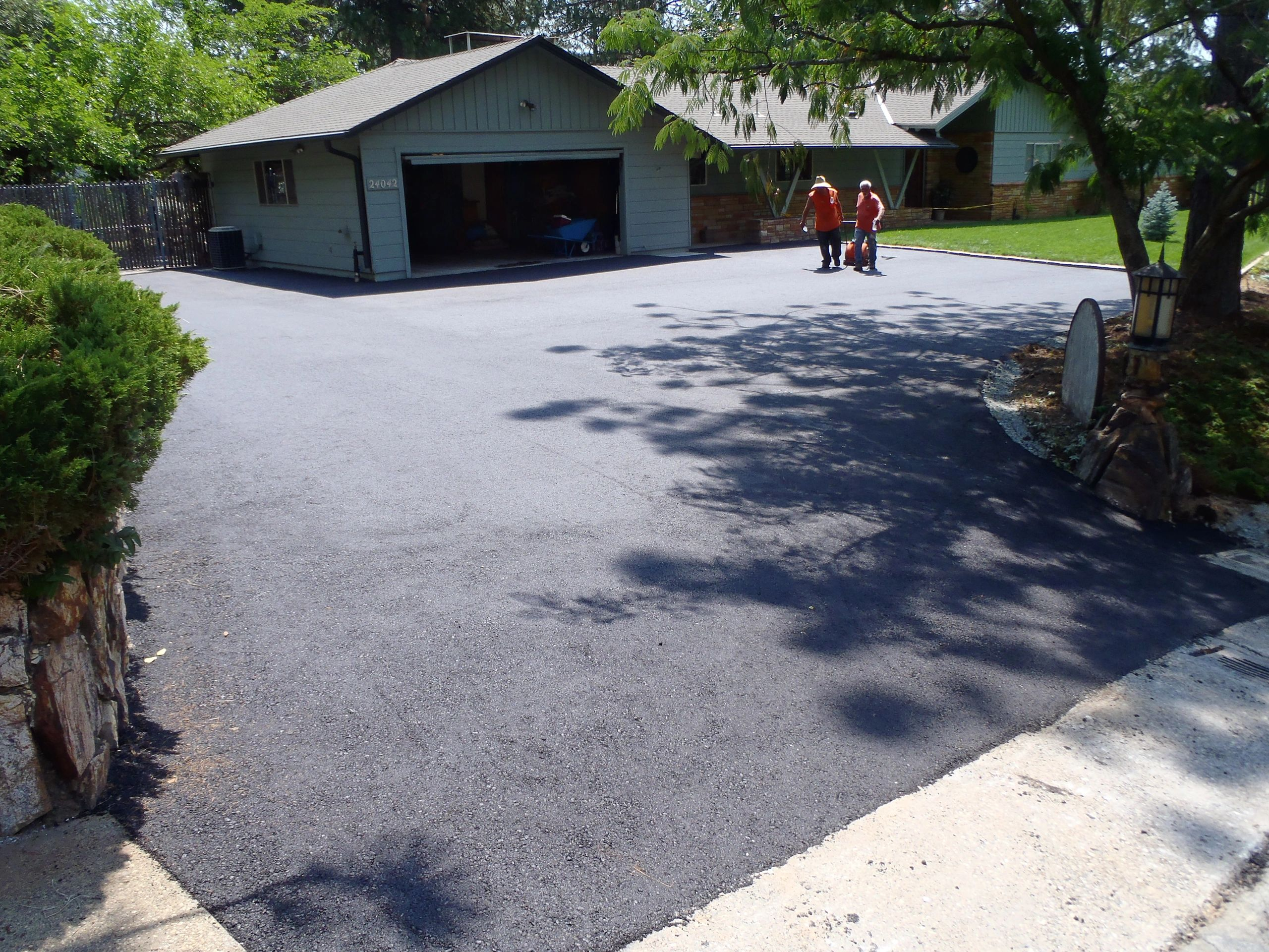 Newly paved asphalt driveway with two crew members and house in the distance