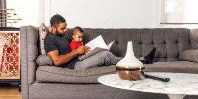 Black father and son reading together on clean couch