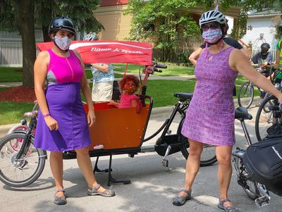 Two women wearing helmets and masks. Cargo bike with child wearing mask.
