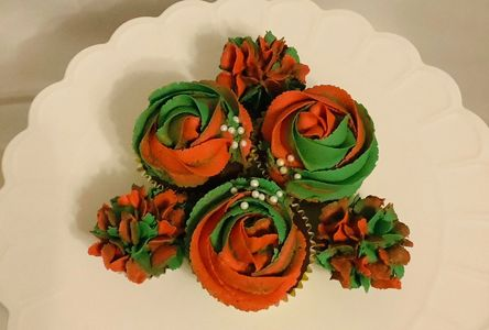 Cupcakes swirled with a green and red rose,