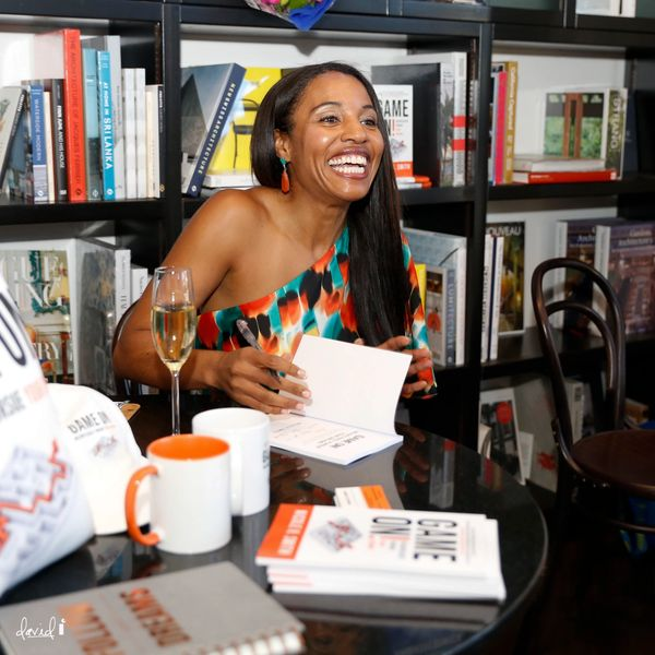 Author smiling sitting at a table with pen in hand preparing to autograph her book.