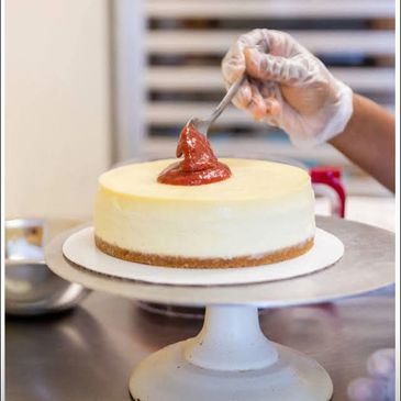 A classic original cheesecake with a strawberry topping on a cake stand