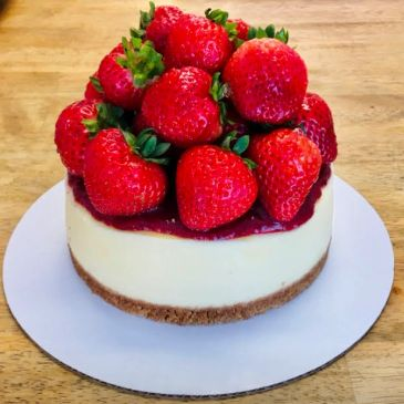 Classic original cheesecake topped with fresh strawberry sauce and strawberries