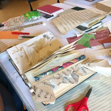 Image of book arts workshop table with projects being constructed.