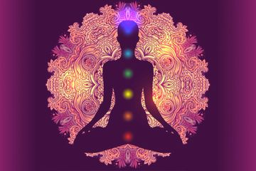 Silhouette of a person sitting, the 7 colors of Chakras are going up the center of their body.