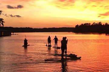 group of people paddle boarding on a lake at sunset