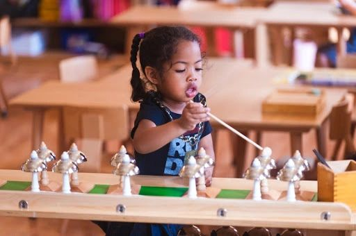 A child playing Montessori bells