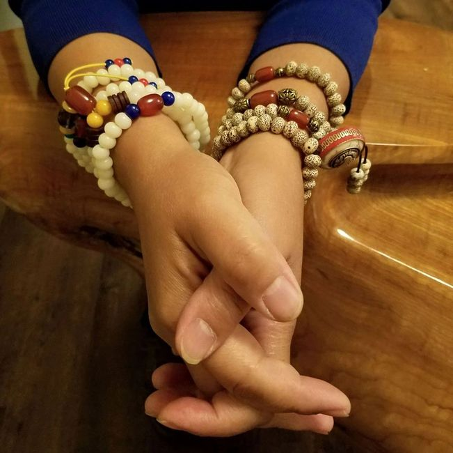 A woman's clasped hands with both wrists adorned with Buddhist mala beads.