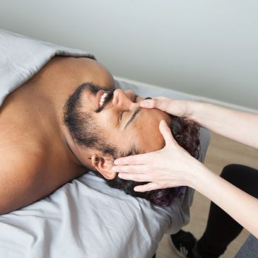 Man lying on massage table face up having his forehead massaged