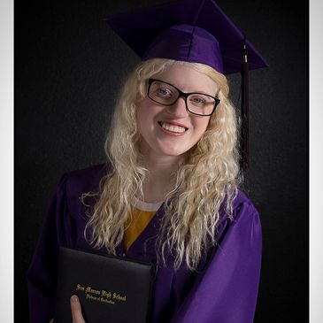 San Marcos High school senior wearing her purple cap and gown.