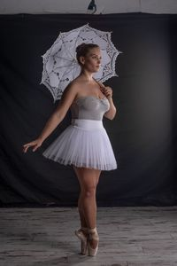 Before Image of a portrait image of a ballerina with a white umbrella.