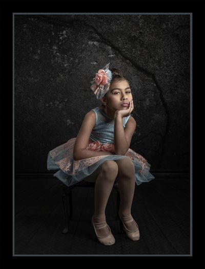 Fine Art Studio portrait of a little girl in blue and peach color ballerina dress.