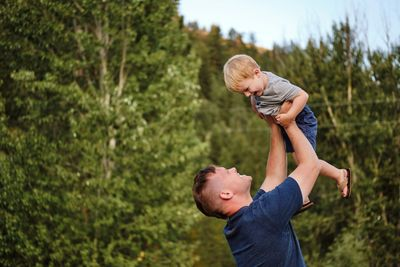 Father holding his boy up in the air during a  family photography session in Missoula Montana.