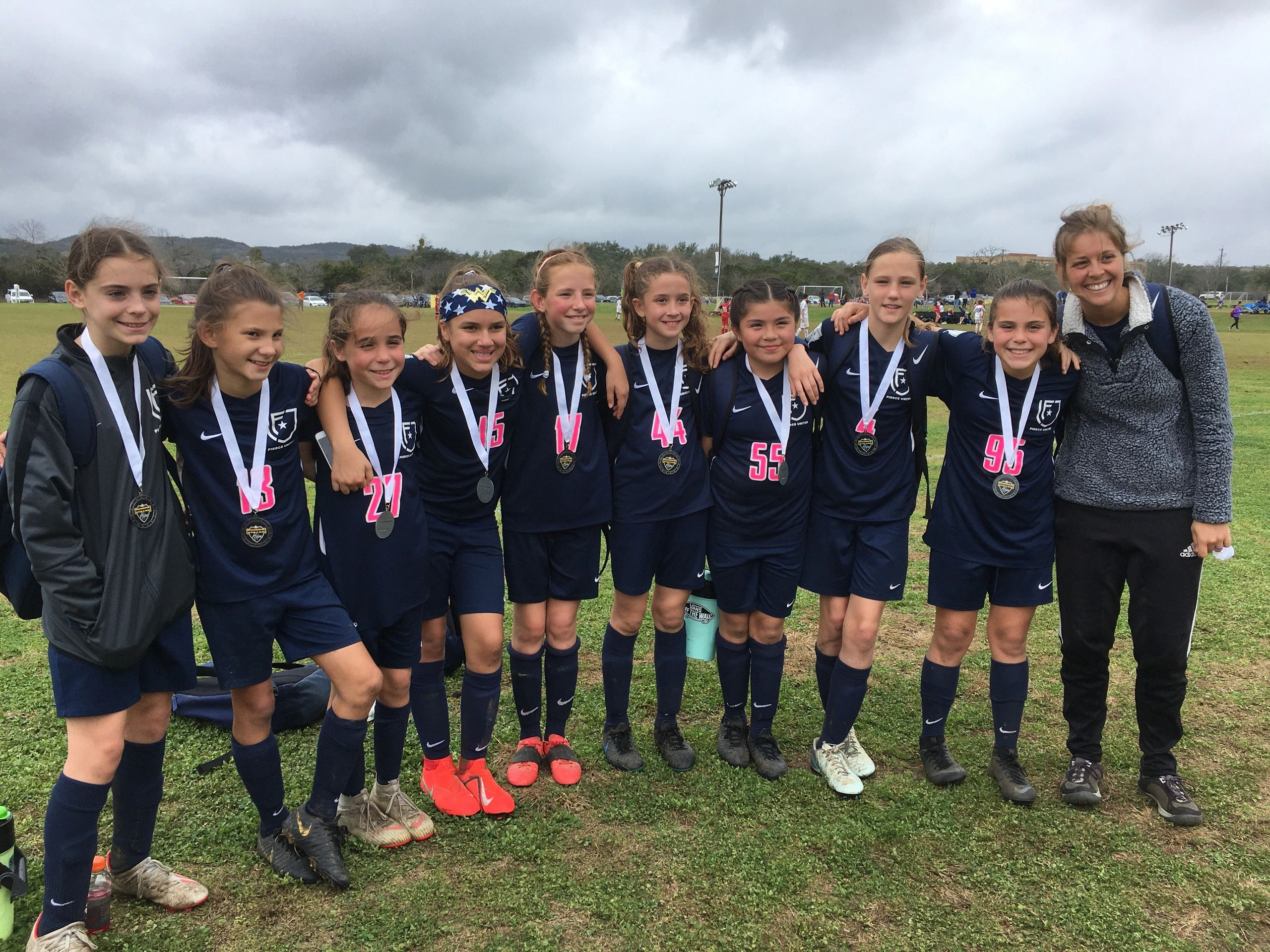 09 girls celebrate another tournament title with one of our female coaches