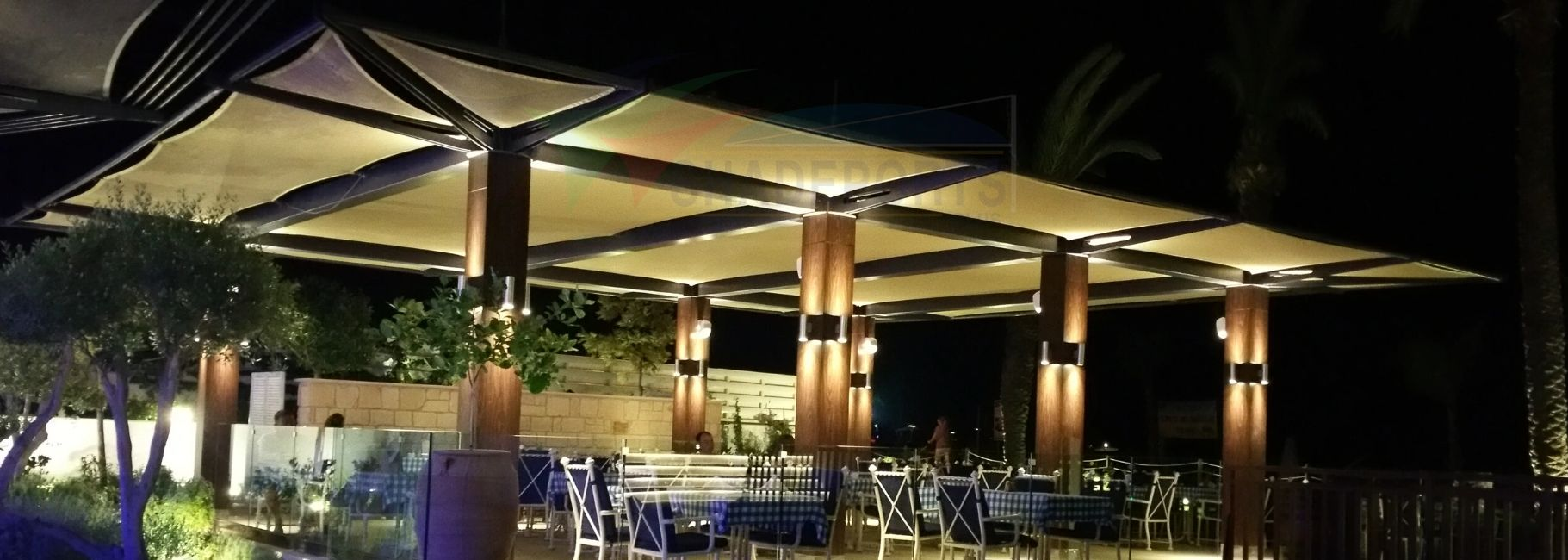 Shade structure at night with integrated outdoor lighting, by Shadeports Plus Ltd, Cyprus.