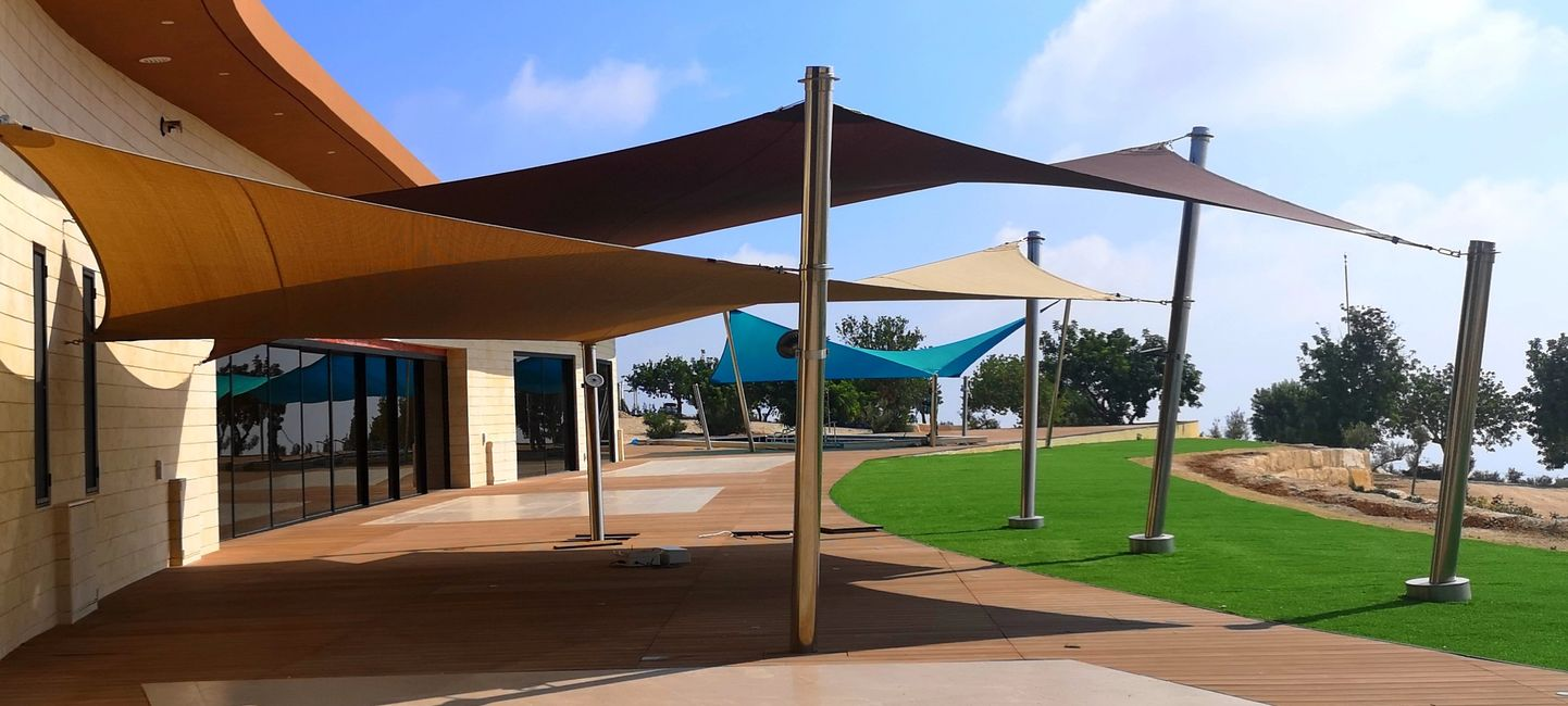 Custom shade sails with stainless steel poles over decked area.