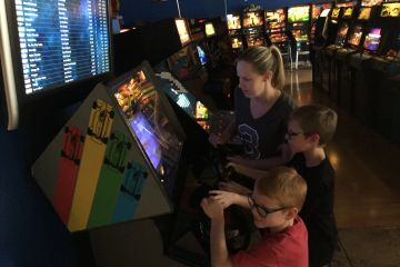 Family playing Atari's Super Sprint racing game in the arcade.