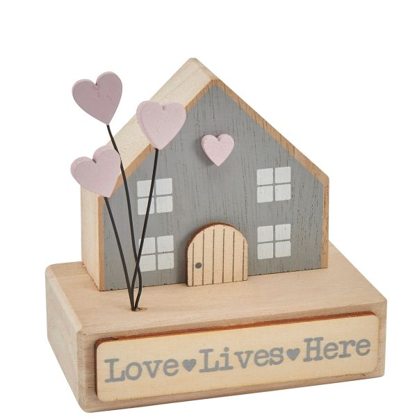 'Love lives here' wooden house on base