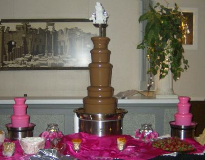 Large chocolate fountain, with 2 small white chocolate fountains colored pink on each sides.