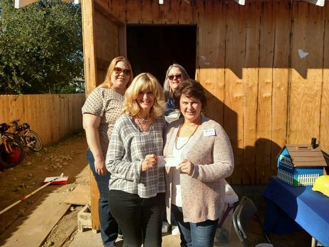 Board Members, Nancy Mannon, Jessica Morley and Lottie Miller give Habitat for Humanity a $1000 chec