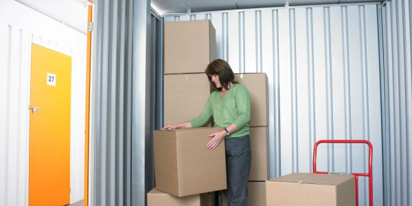 Woman in a container room carrying objects for a business