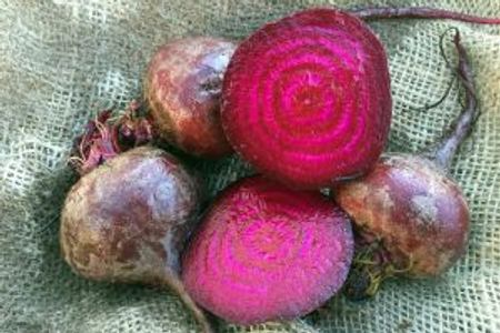 photo of red beets on burlap, one is cut open to show deep red interior