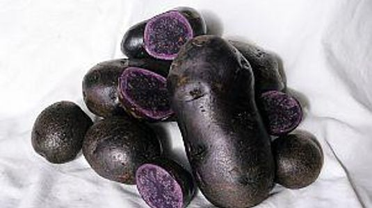 Deep purple potatoes, one cut open to show deep purple inside, rimmed with a light purple perimetre
