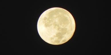 Creamy full moon close up with dark spots and craters visible