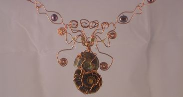 Two ammonite fossils wrapped in copper wire to look like a sea creature. Pendant on wire necklace.