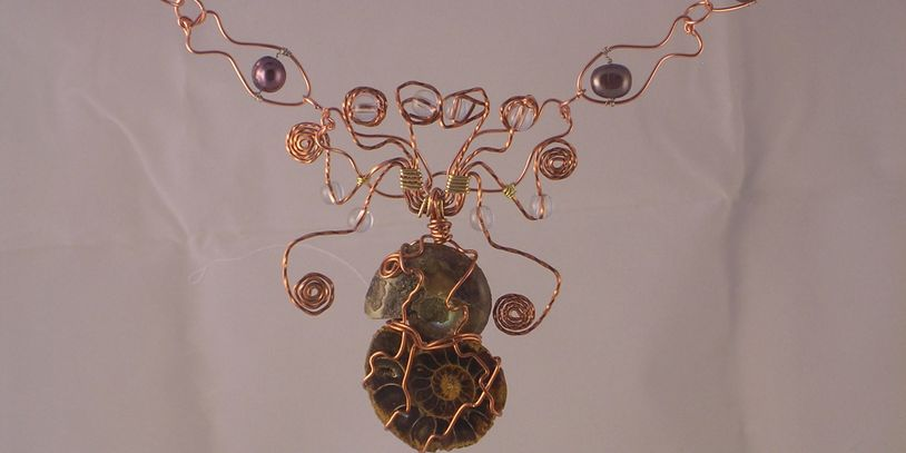 Ammonite fossils wrapped in copper wire