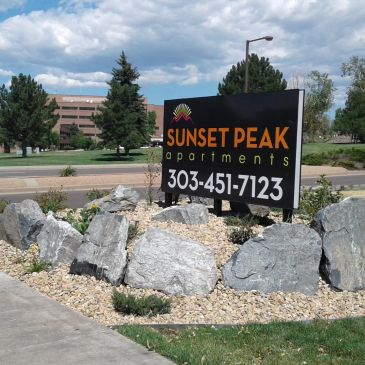 Landscape install with boulders, rock, plantings, and property sign.
