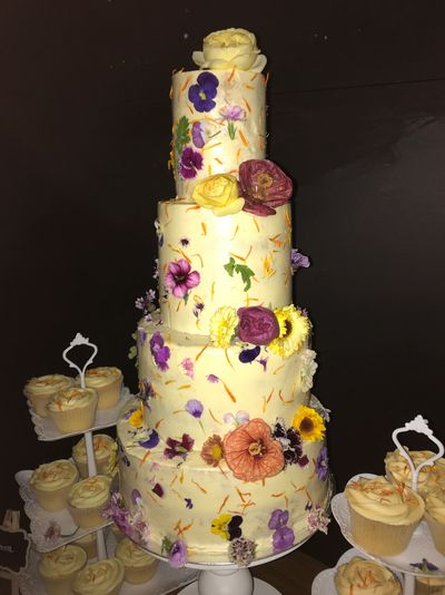 A Rustic Organic Edible Flower Cake both pressed onto the cake and set cascading down