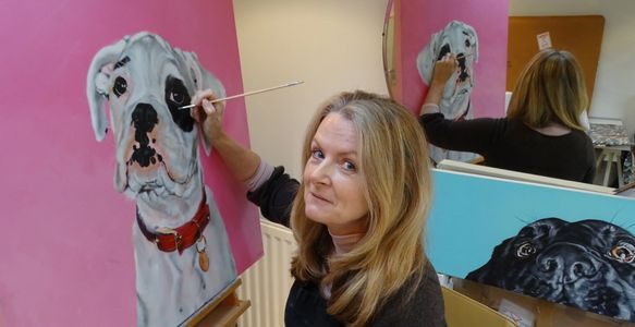 Carol Gillan in studio painting a commission in oils of a Boxer Dog