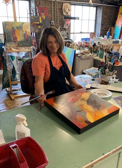 Myra Dwyer working in the Pushin Building Artists' Studio on an abstract painting on a cradleboard.