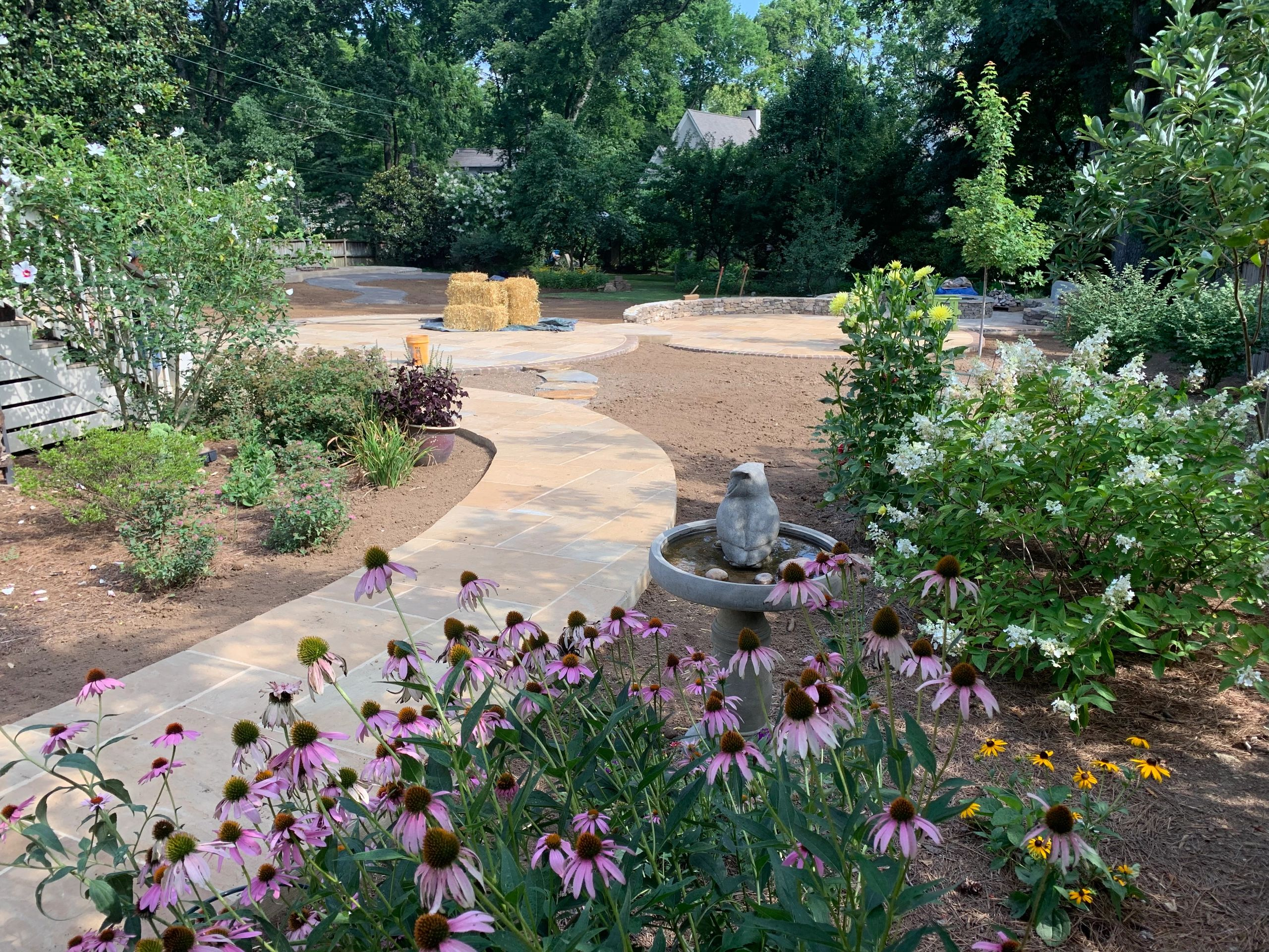 walkway installation leading to backyard circle patio design