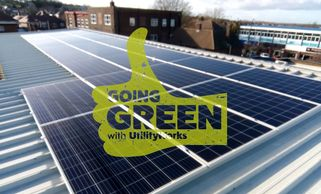 GREEN THUMB WITH TEXT OF UTILITY WORKS IN IT, WITH SOLAR PANELS BEHIND THUNB