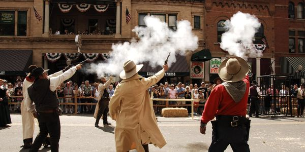 Men in old western dress shooting at the sky with smoke in front of old bar