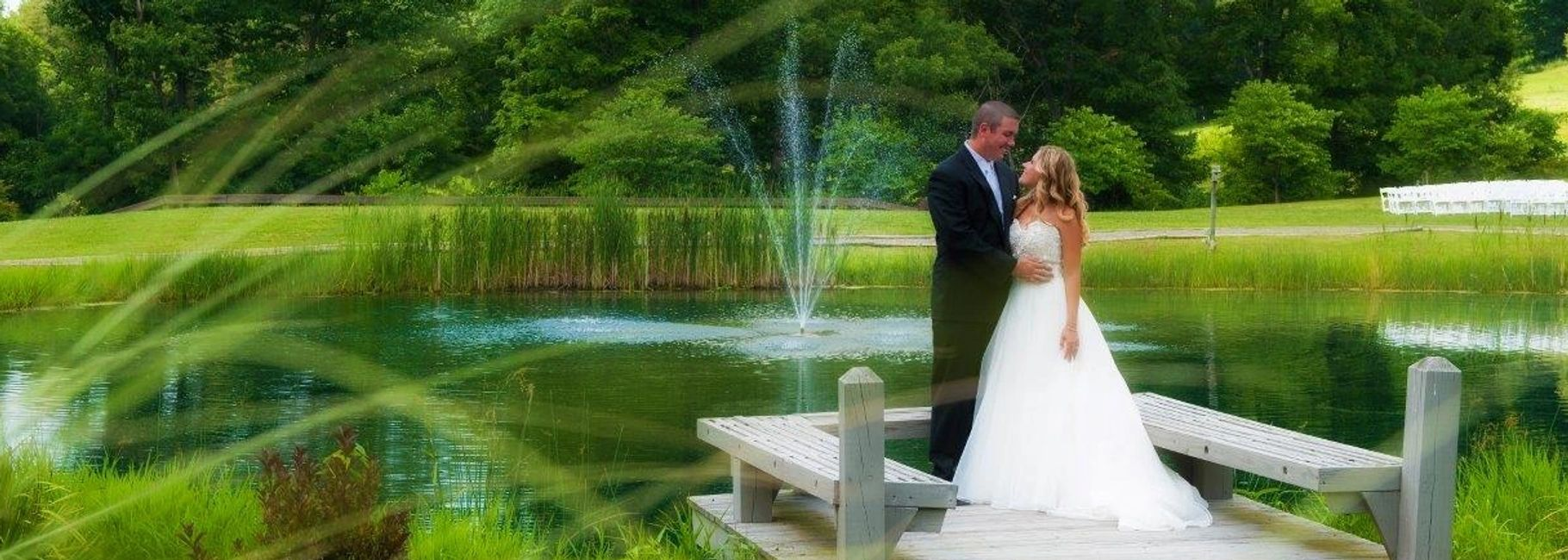 a bride and groom looking over our vineyard pond