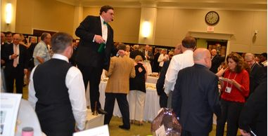 A Parker Fundraising Auctioneer working an art sale and tasting event.