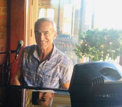 A smiling Mike Petrone seated at the piano in the Brothers Lounge Wine Bar.